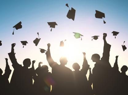 photo of graduates tossing their caps